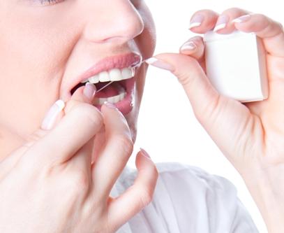 Young woman flossing teeth , studio shot