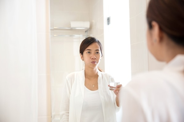 A portraiyt of an Asian young woman gargle on her mouth after tooth brushing